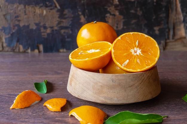Frutas frescas de laranja em uma tigela de madeira