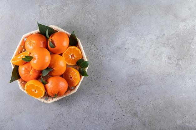 Frutas frescas de laranja fatiadas e inteiras com folhas colocadas em uma cesta de vime