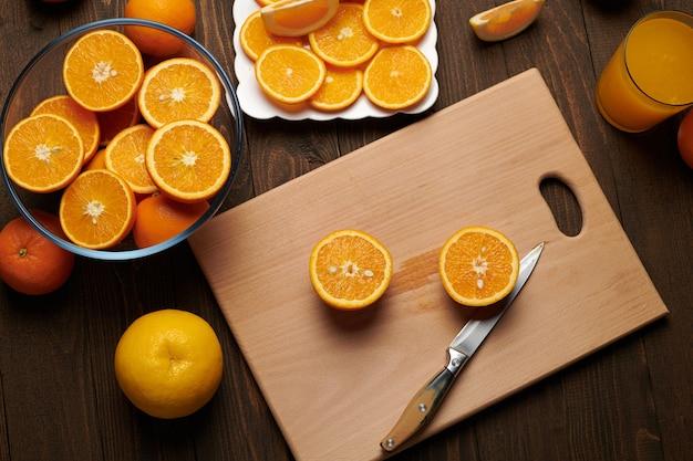 Frutas frescas de laranja inteiras e fatiadas em uma mesa de madeira, cortando b