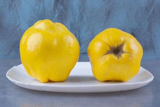 Frutas frescas de marmelo no prato na superfície escura