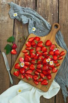 Frutas frescas de morango, flores, folhas na mesa de madeira branca
