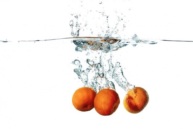 Frutas frescas de tangerina, caindo em respingos de água