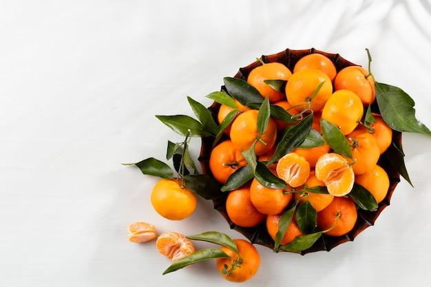 Frutas frescas de tangerina com folhas em caixa de madeira, vista superior.