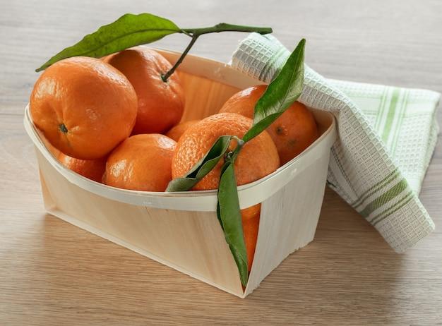 Frutas frescas de tangerina com folhas na mesa de madeira