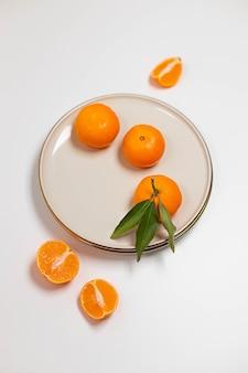 Frutas frescas de tangerina ou clementina em um prato bege com uma borda de ouro sobre fundo branco colorido fr ...
