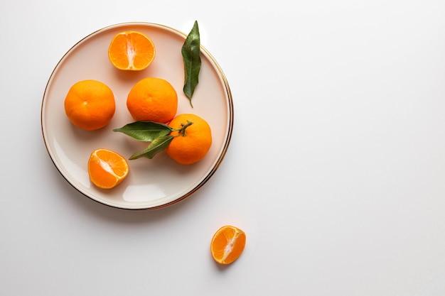 Frutas frescas de tangerina ou clementina em um prato bege