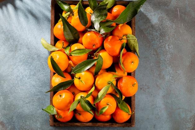 Frutas frescas de tangerina ou tangerinas com folhas em caixa de madeira, vista superior
