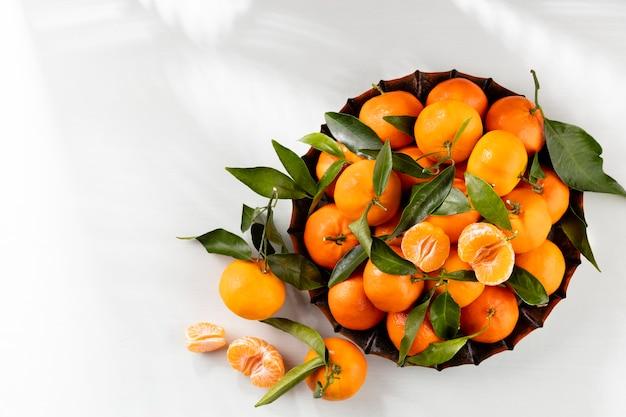 Frutas frescas de tangerina ou tangerinas com folhas em caixa de madeira
