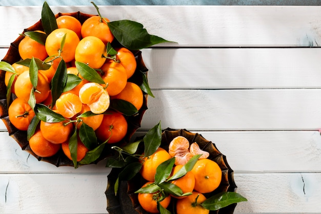 Frutas frescas de tangerina ou tangerinas com folhas em uma caixa de madeira, vista superior