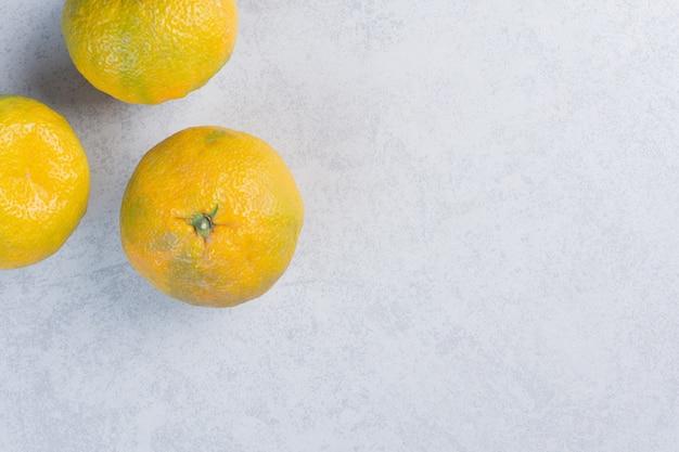 Frutas frescas de tangerina ou tangerinas em fundo cinza.