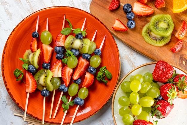 Frutas frescas de verão em palitos. morangos, uvas, mirtilos e kiwi numa apresentação original. lanche leve para um banquete de verão.
