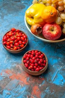 Frutas frescas de vista frontal com bagas em fundo azul foto colorida madura dieta saúde