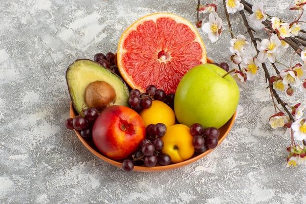 Frutas frescas de vista frontal dentro do prato na superfície branca
