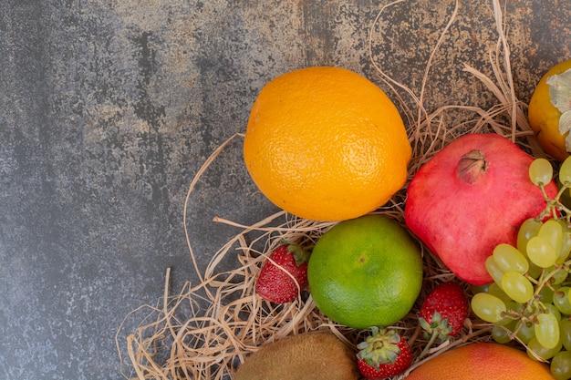 Frutas frescas diferentes no espaço de mármore.