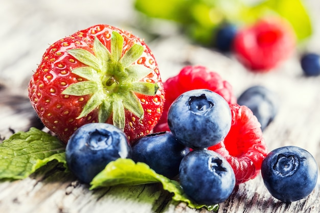 Frutas frescas do verão: delicioso morango, lindas framboesas com mirtilos em uma aromática hortelã verde.