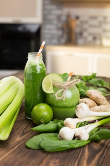 Frutas frescas e garrafa com smoothies verdes na mesa da cozinha