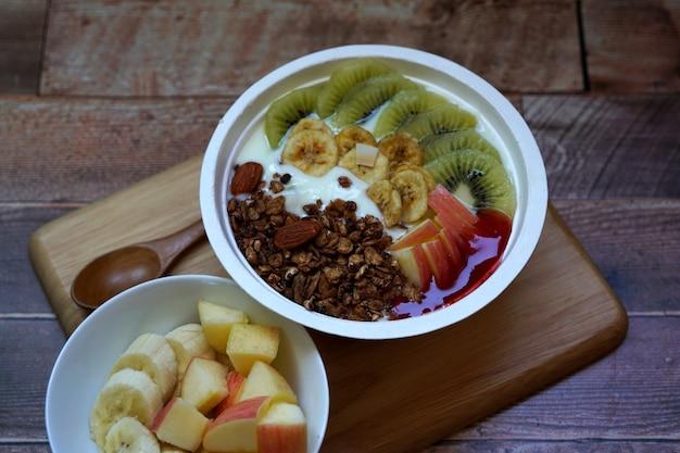 Frutas frescas e granola com iogurte em uma tigela sobre uma mesa de madeira