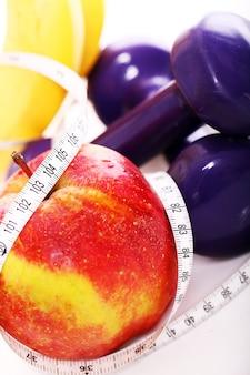 Frutas frescas e halteres com fita métrica