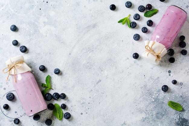 Frutas frescas e saudáveis de smoothie de mirtilos e hortelã em frasco de vidro na superfície de concreto branco