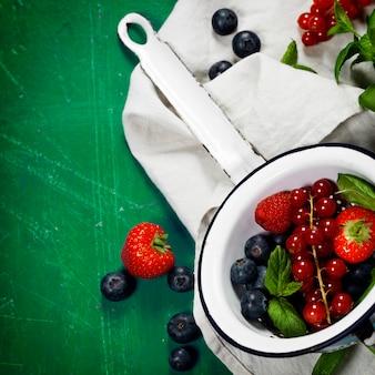 Frutas frescas em fundo de madeira. morangos, framboesas e Foto Premium