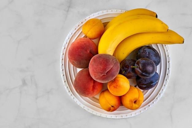 Frutas frescas em um prato branco sobre uma mesa de mármore branco.