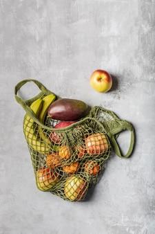Frutas frescas em um saco de corda verde sobre uma mesa cinza clara. bananas, maçãs, laranjas e mangas.