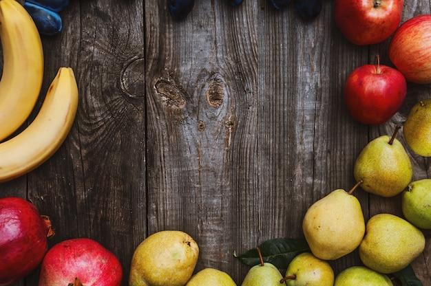Frutas frescas em uma superfície de madeira cinza, bananas, maçãs, ameixas e peras