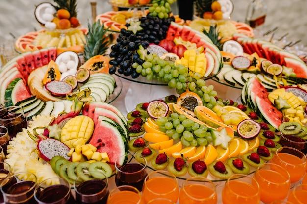 Frutas frescas, exóticas e orgânicas, lanches leves em um prato na mesa de buffet. diversos mini petiscos e petiscos, comida de restaurante no evento. mesa deliciosa decorada para guloseimas de festa.