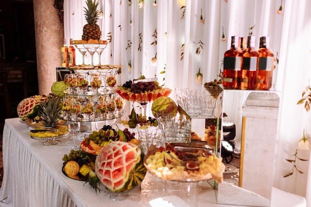 Frutas frescas, exóticas, orgânicas, lanches leves em um prato sobre uma mesa de buffet. mini iguarias e lanches variados, comida de restaurante no evento. deliciosa mesa decorada para presentear uma festa.