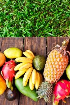 Frutas frescas. frutas exóticas misturadas em fundo de madeira. alimentação saudável, dieta saudável. vista superior com espaço de cópia de grama