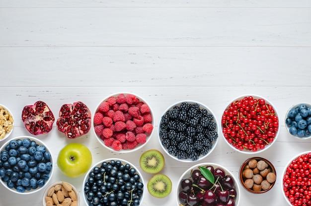 Frutas frescas, frutas nozes em um fundo branco de madeira, o conceito de alimentação saudável contém v