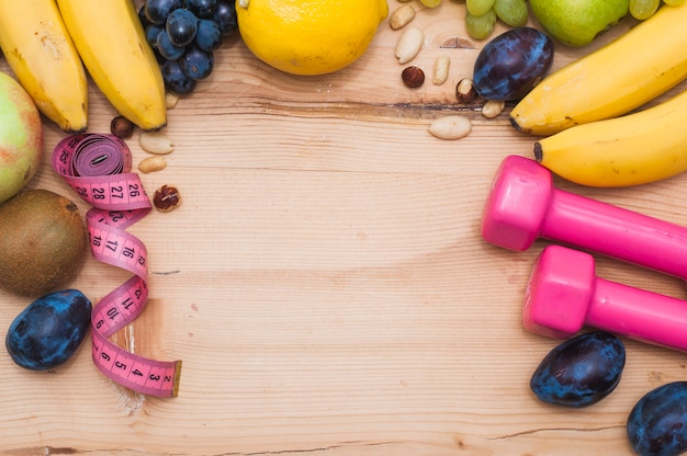Frutas frescas; frutas secas; fita métrica e halteres rosa na mesa de madeira