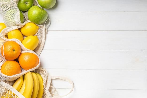 Frutas frescas, maçãs, bananas, laranjas e limões em bolsas ecológicas