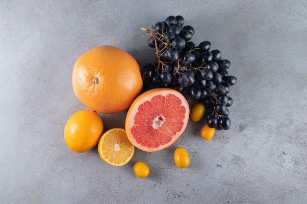 Frutas frescas maduras colocadas sobre uma superfície de pedra.