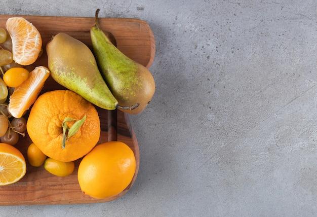 Frutas frescas maduras em uma tábua de madeira colocada sobre um fundo de pedra.