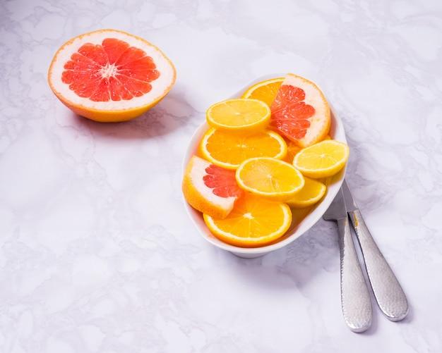 Frutas frescas misturadas alimentação saudável dieta alimentar saudável de frutas cítricas, laranjas, limões e toranja no fundo branco e placa