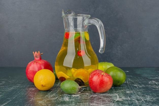 Frutas frescas misturadas e um copo de suco na mesa de mármore.