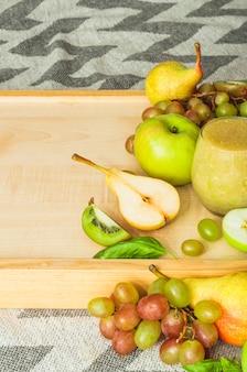 Frutas frescas na bandeja de madeira contra a toalha de mesa