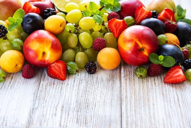 Frutas frescas no verão e bagas em uma mesa de madeira branca