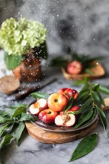 Frutas frescas pêssegos com folhas em um close-up de placa.