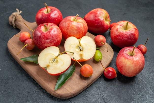 Frutas frutas e bagas na placa de madeira ao lado das maçãs com folhas
