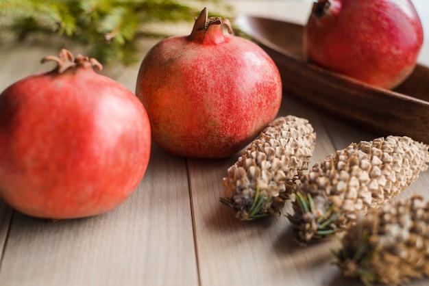 Frutas granada de natal, galho de árvore spruce e grandes saliências em um plano de fundo texturizado