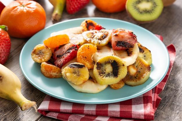 Frutas grelhadas em prato azul e mesa de madeira branca