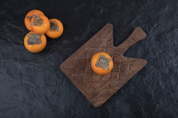 Frutas inteiras de caqui fuyu na tábua de madeira