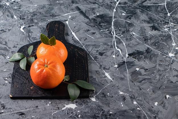 Frutas inteiras de laranja frescas com folhas colocadas em uma tábua de corte preta