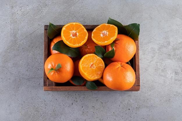 Frutas inteiras e fatiadas de laranja com folhas colocadas em uma velha caixa de madeira