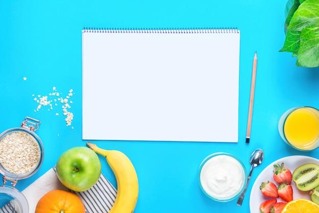 Frutas, iogurte, aveia e bloco de notas em branco sobre fundo azul da mesa.