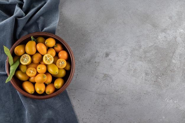 Frutas kumquat em uma tigela sobre um pedaço de tecido, sobre a mesa de mármore.