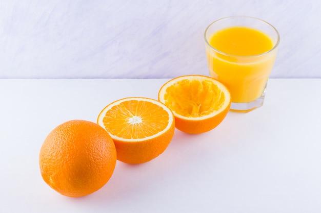 Frutas laranja com suco, conceito. suco de laranja e metades de laranjas. citrus para fazer suco. laranjas inteiras e espremidas e copo de suco