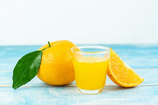 Frutas laranja e suco de laranja na mesa de madeira